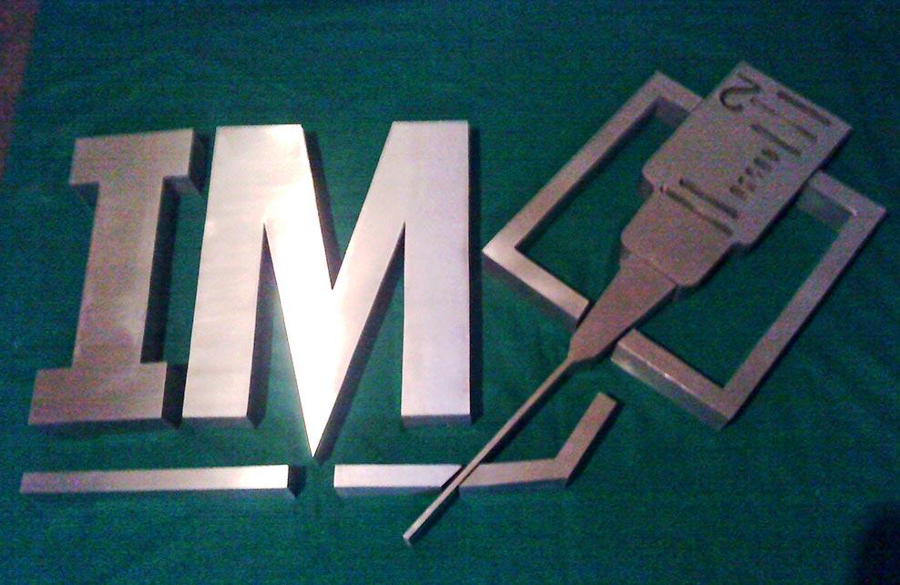 IM - Logotipo armado tipo 3D en acero inoxidable, terminado satinado mate.