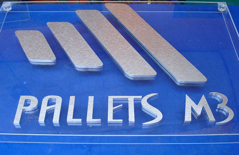 PALLETS M3 - Letrero armado tipo 3D en aluminio natural, terminado mate, montado sobre acrílico transparente.