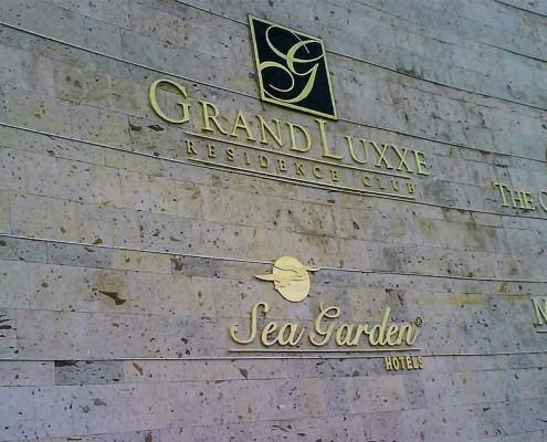 GRAND LUXXE - Letras y logotipos fundidos en bronce, terminado mate, en medida aproximada de 80 cm de alto.